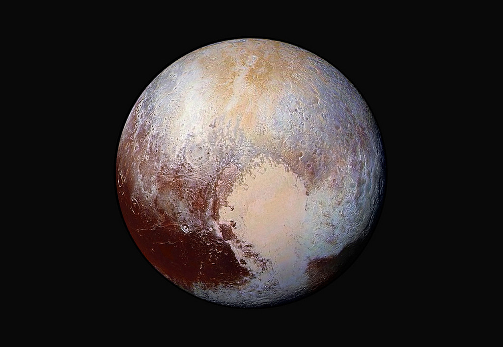 "Pluto may no longer be a planet, but another ""planet nine"" may lurk beyond it. Pluto in false color. Image credit: NASA's Marshall Space Flight Center."